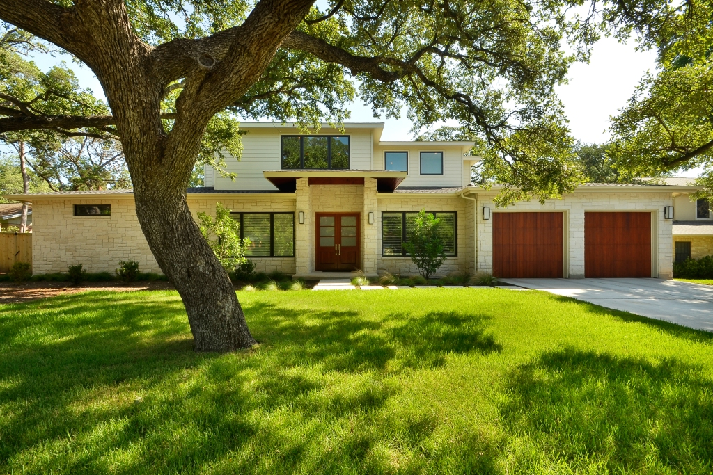 Large leafy tree in a home's front yard provides shade