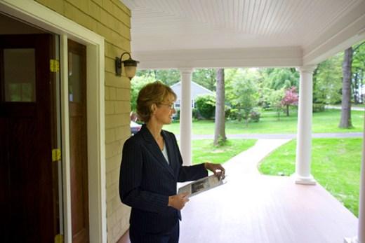 Real estate appraiser outside of a house