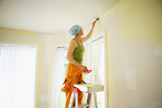 Woman painting wall in preparation for selling her home