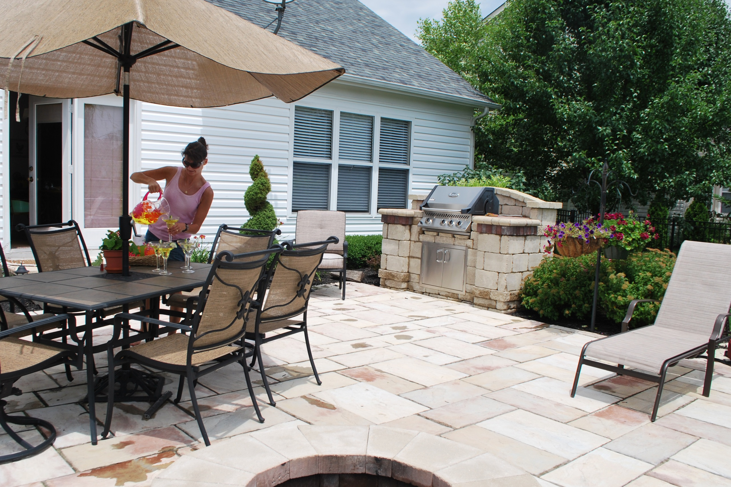 Woman pouring drinks on backyard patio with grill