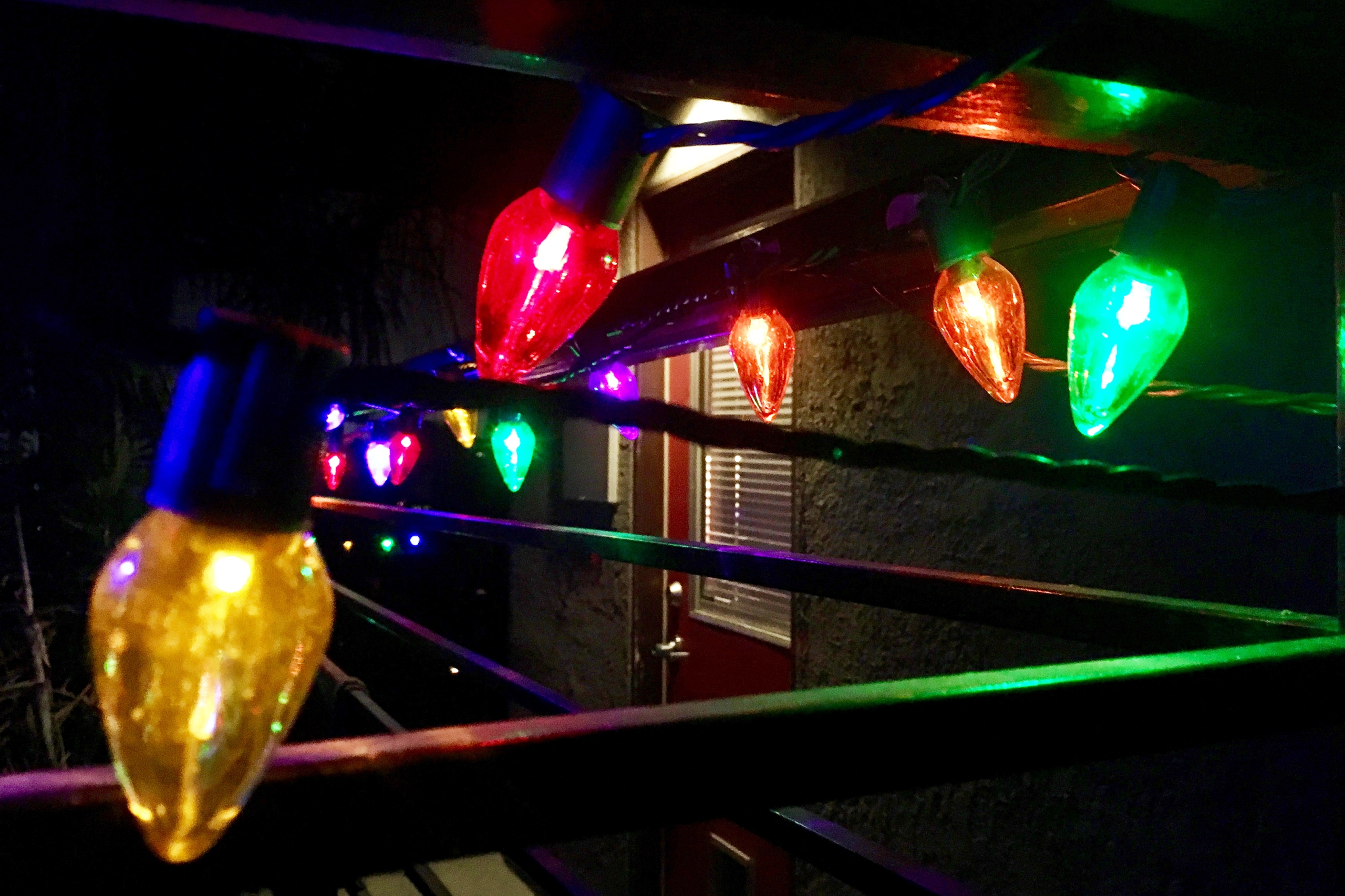 Close up of multi-colored Christmas lights on railing