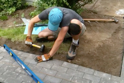 Man with knee pads and gloves installing pavers with hammer