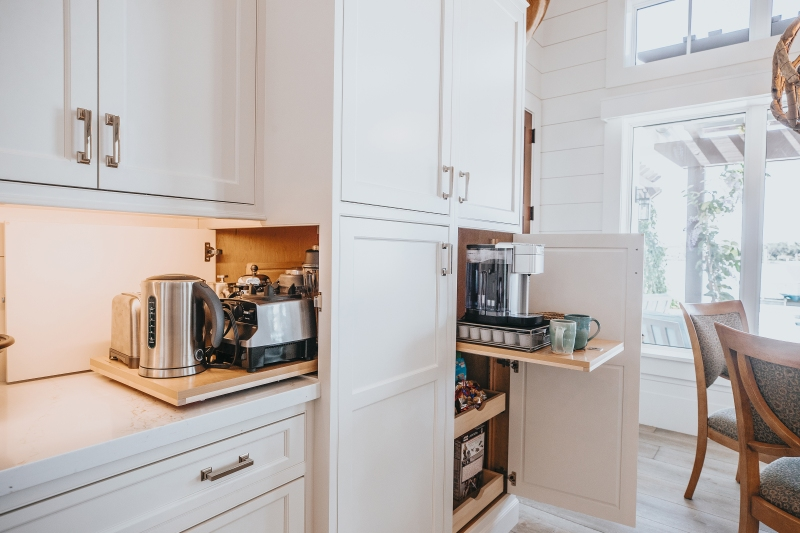 White kitchen with cabinet open to reveal hidden pull out