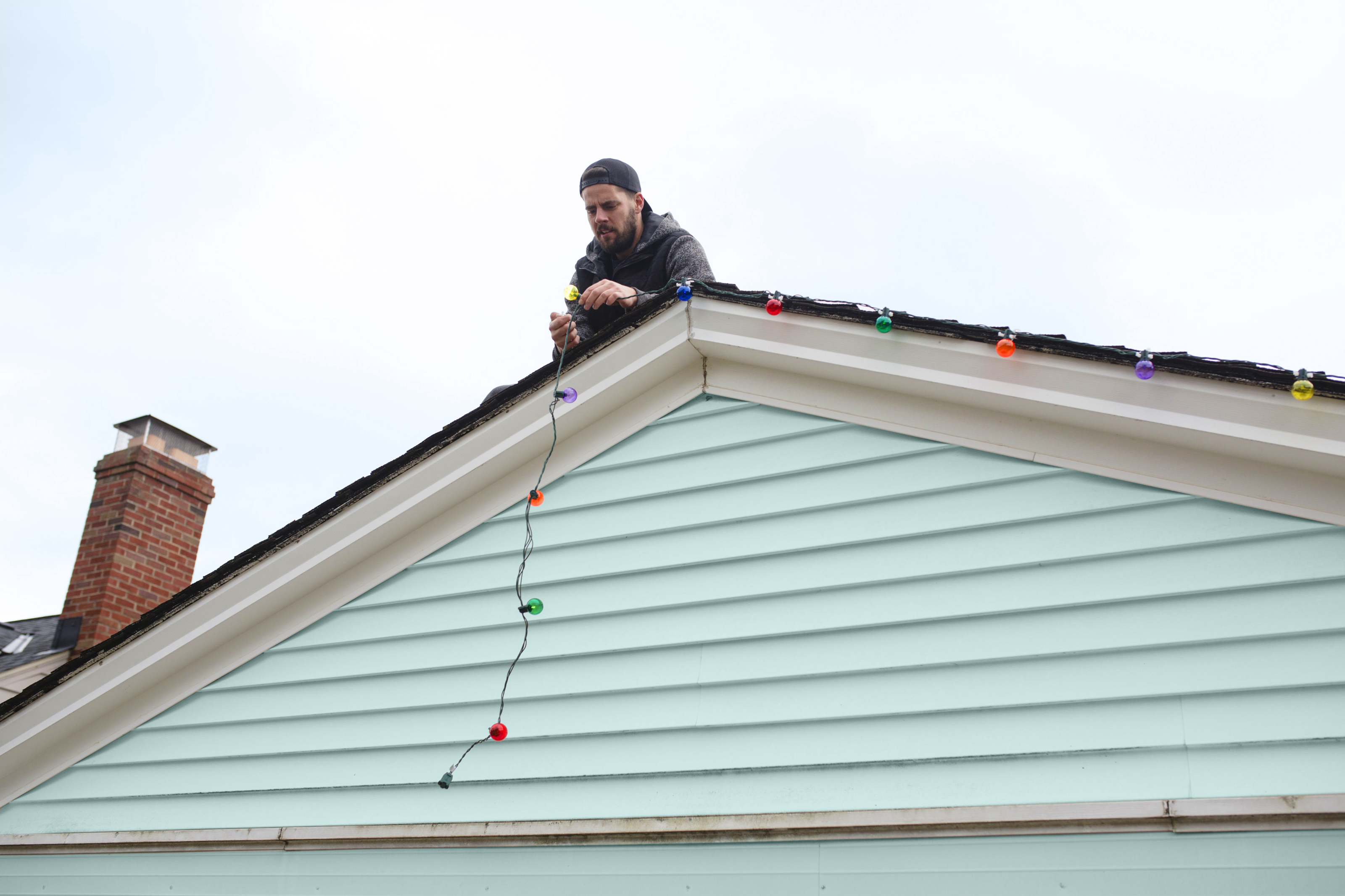 Man on roof hanging string of multi-colored Christmas lights