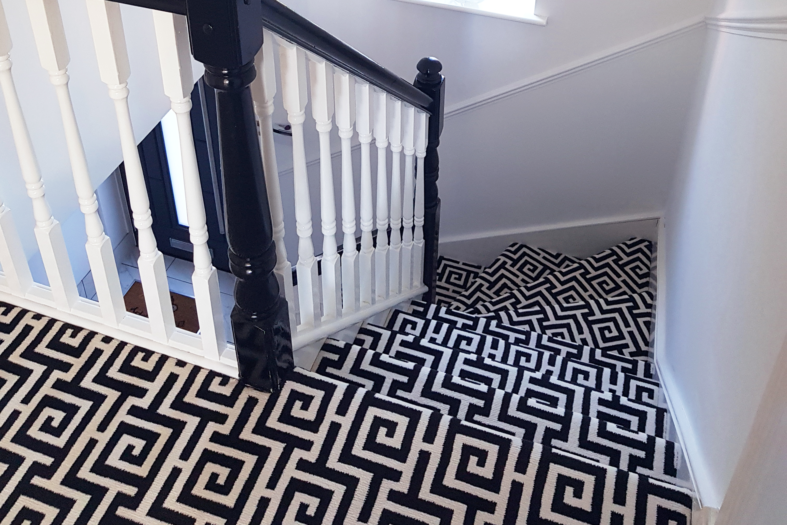 Spiral stairs covered in black and white geometric carpeting
