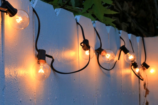 String of globe lights looped along pickets of white fence