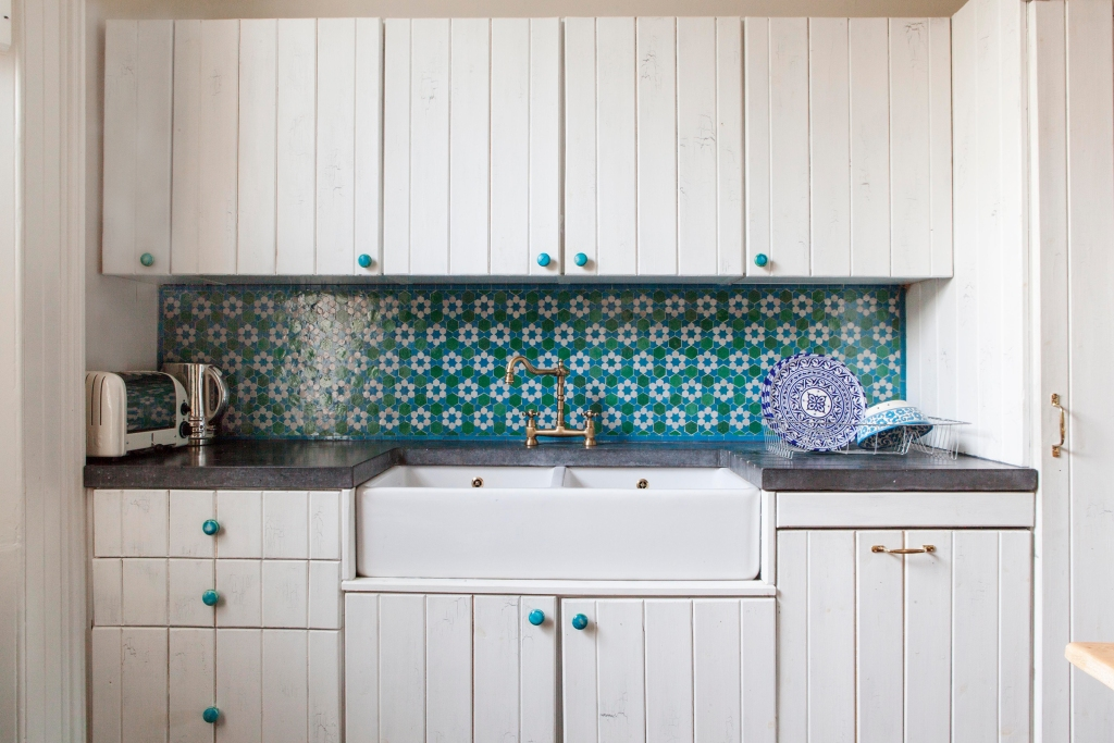 Teal knobs on white cabinets in an eclectic kitchen