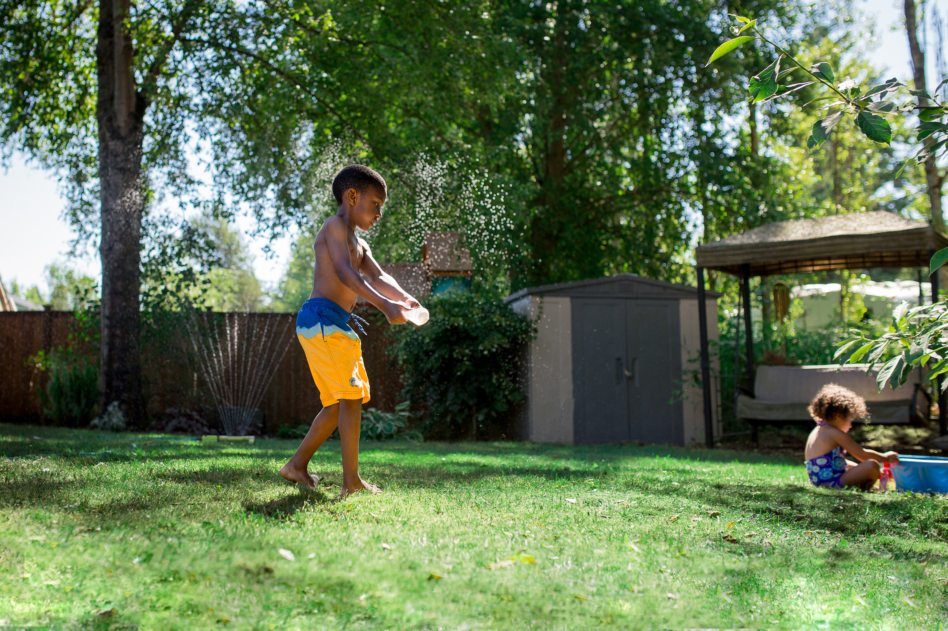 Boy playing a back yard sprinkler in summer