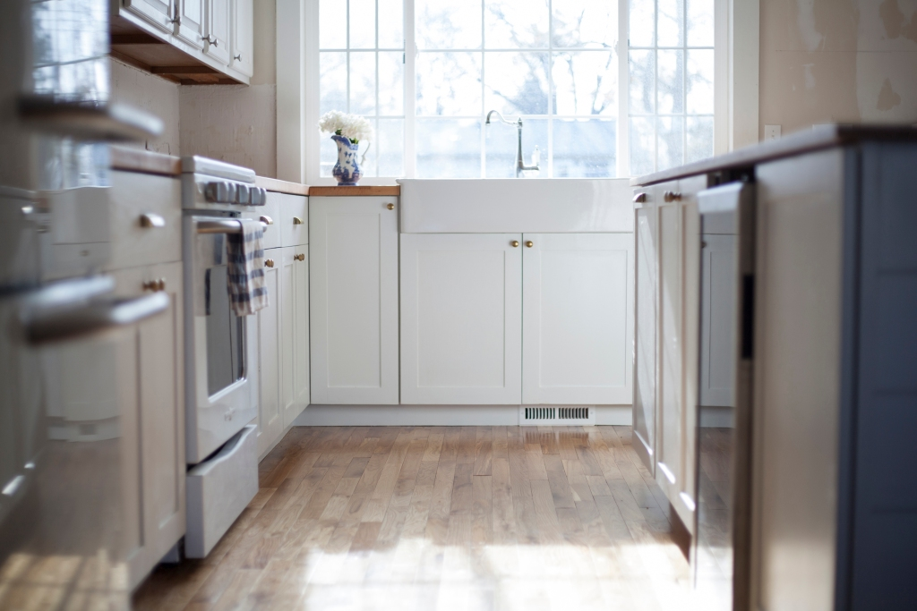 Low view of white kitchen sink and cabinets beneath window