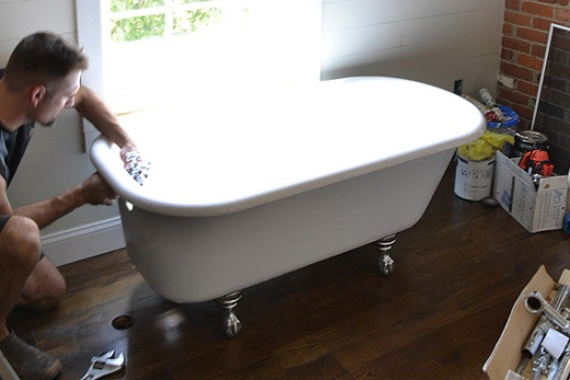 Working on an antique clawfoot tub in a home bathroom