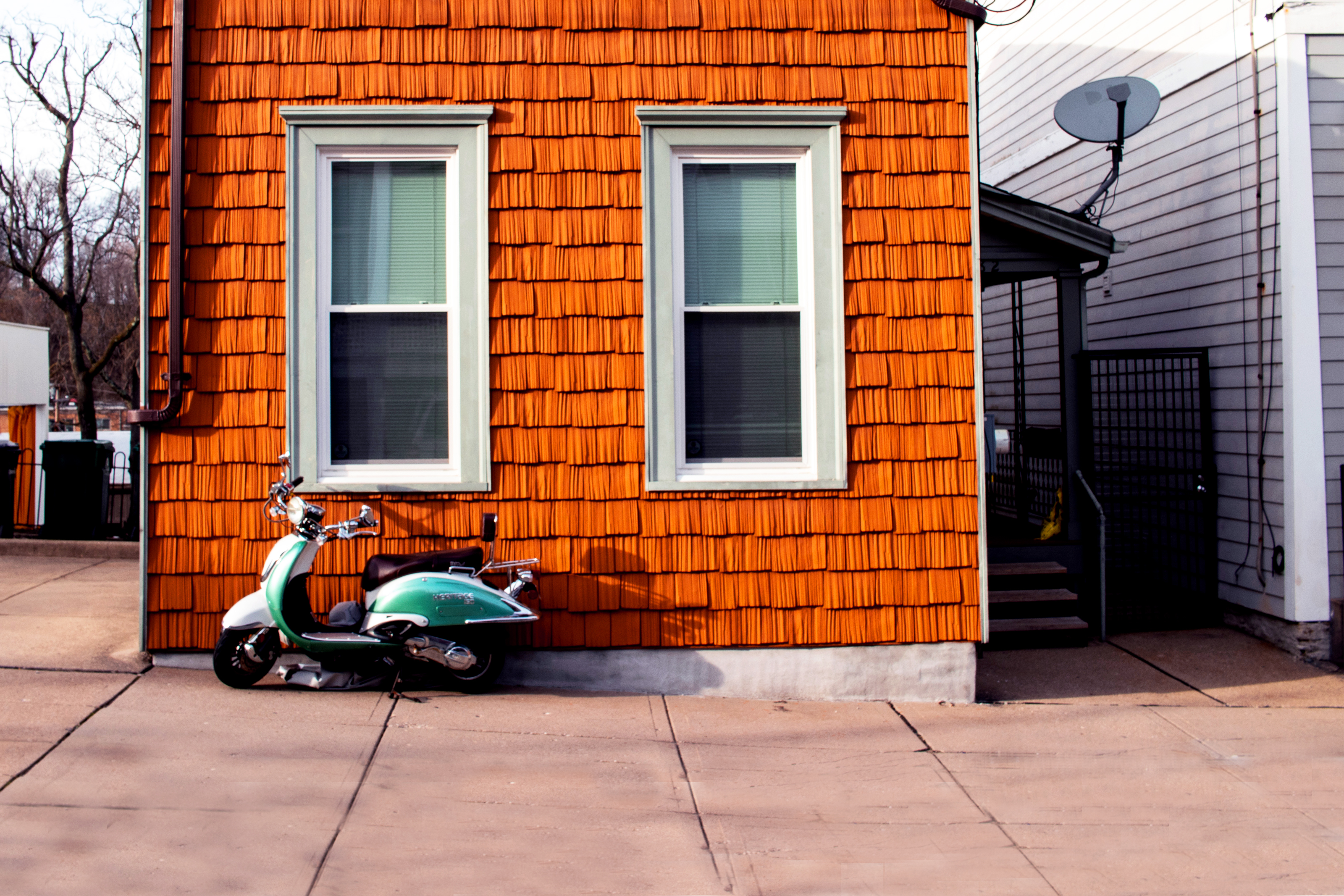 Wood-paneled house with green scooter resting against it