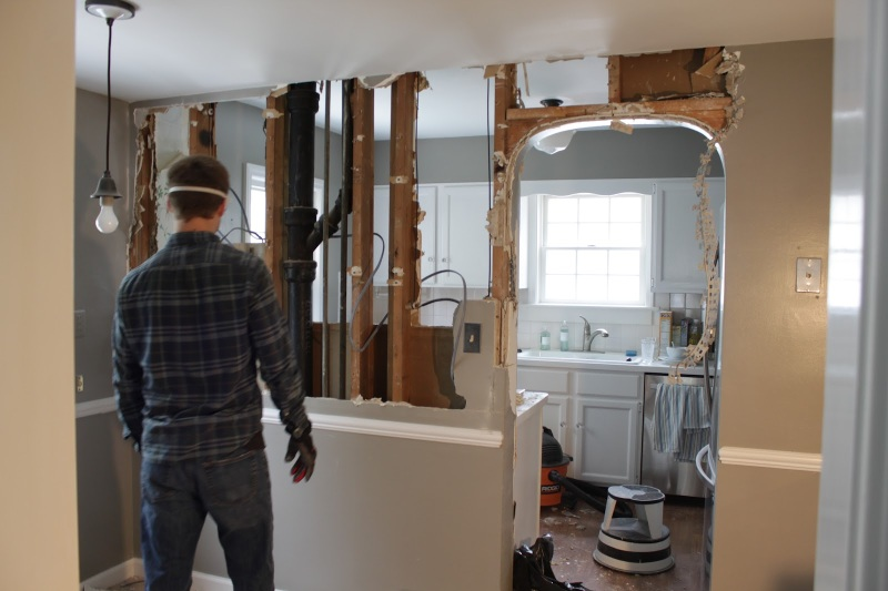 Man demolishing kitchen wall