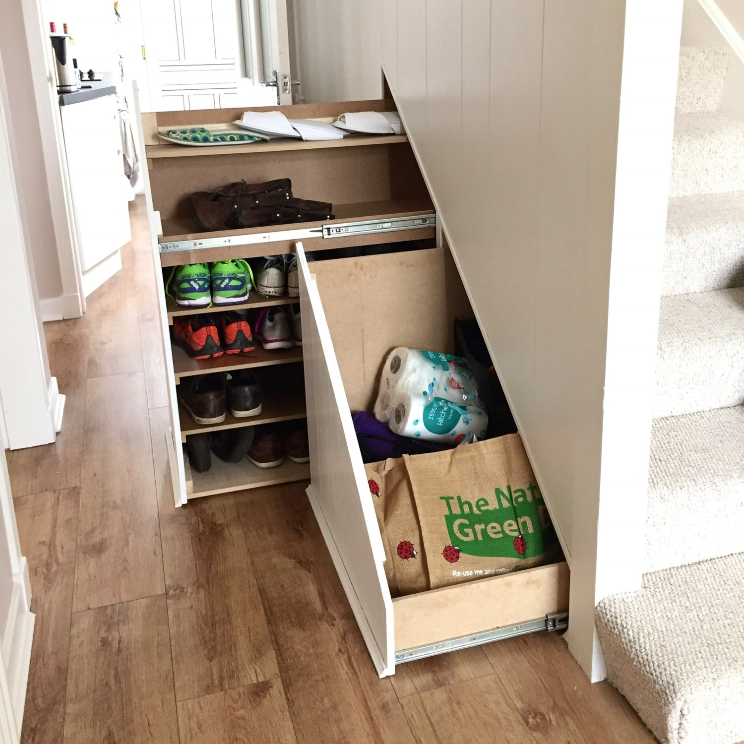 Drawers beneath stairs pull out to reveal bags and shoes