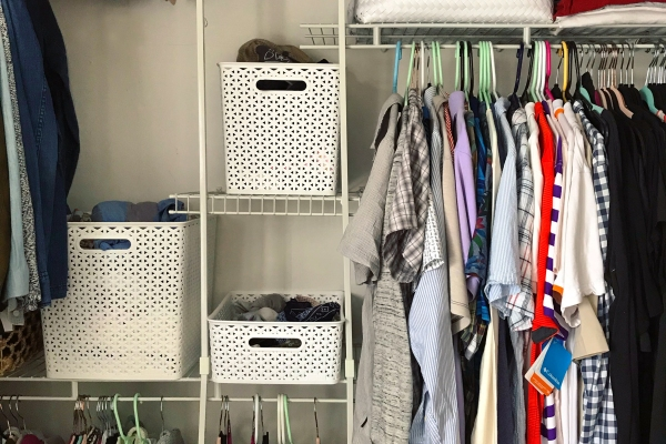 Closet system featuring shirts and four white baskets