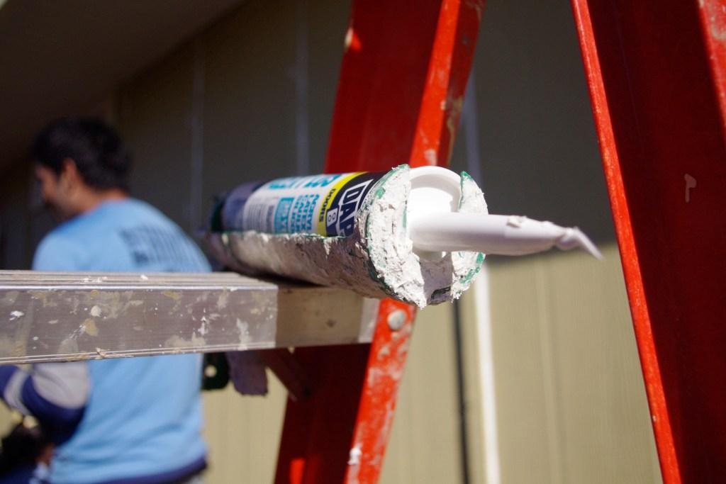 Tube of caulk resting on a ladder