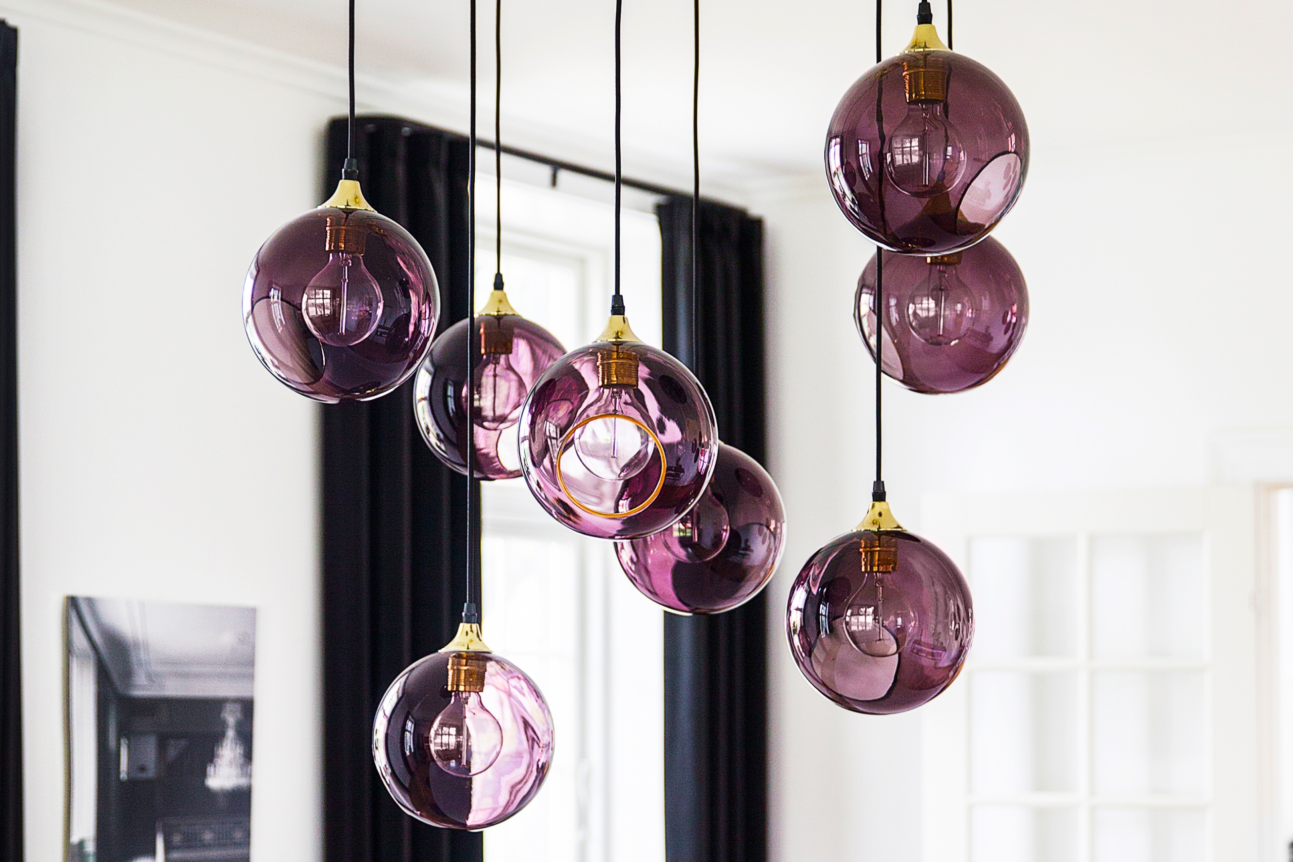 Cluster of purple globe lights hanging in a white room