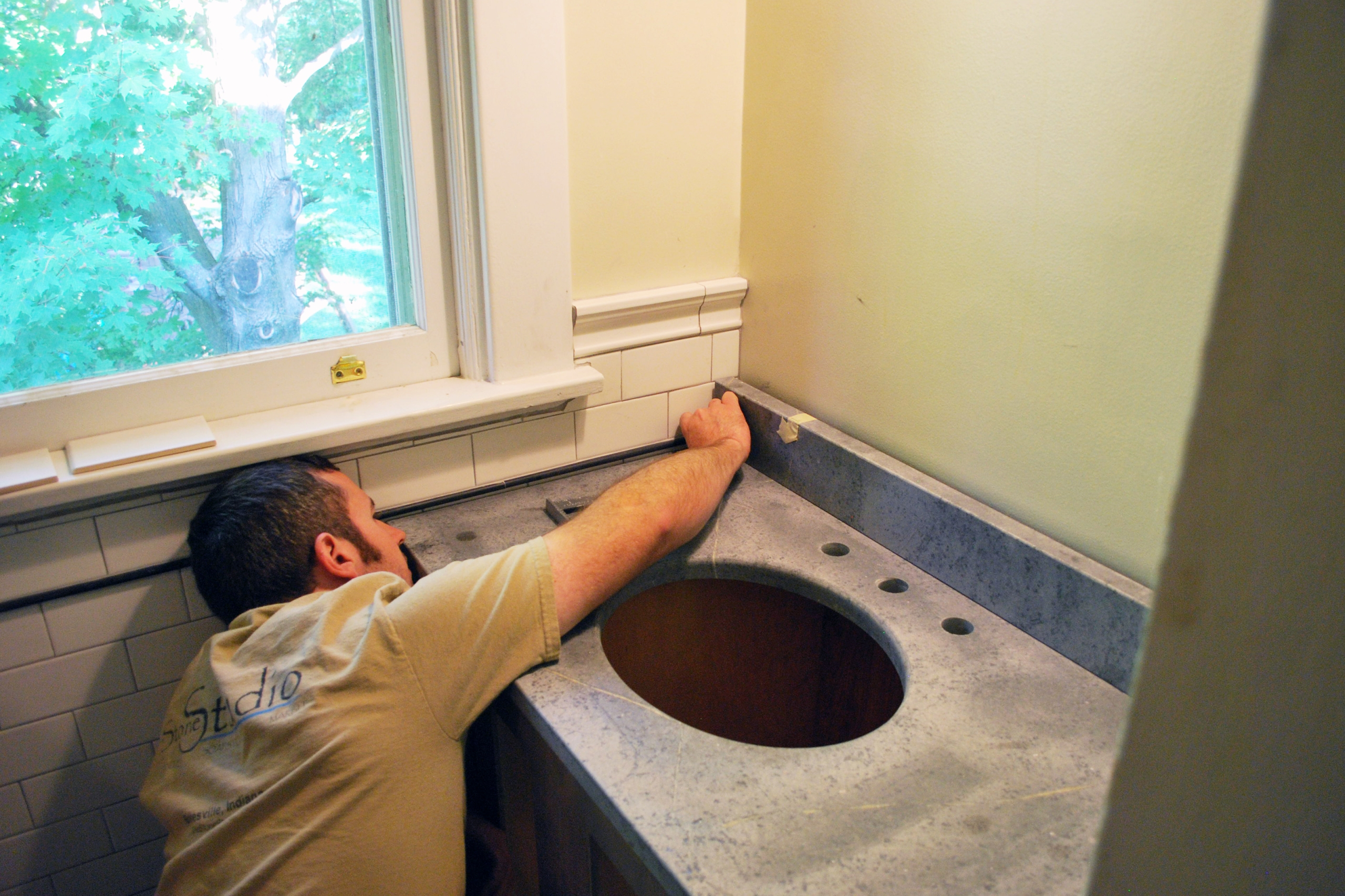 Man installing tile in a bathroom