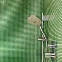 A modern bathroom with a green tile shower