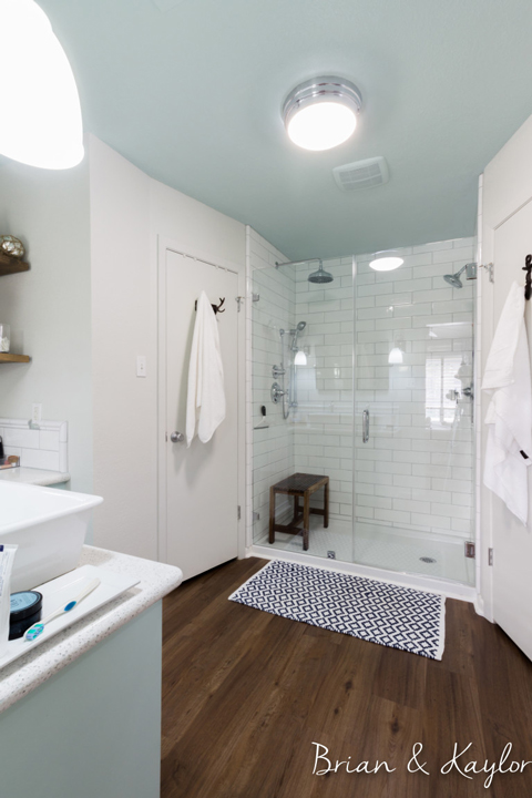 A bright white-walled bathroom with walk-in, tiled shower