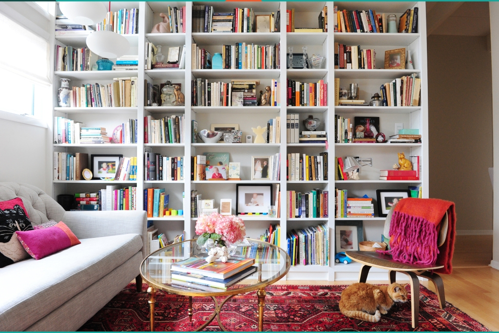 Built-in floor to ceiling bookshelves with grey couch and glass coffee table