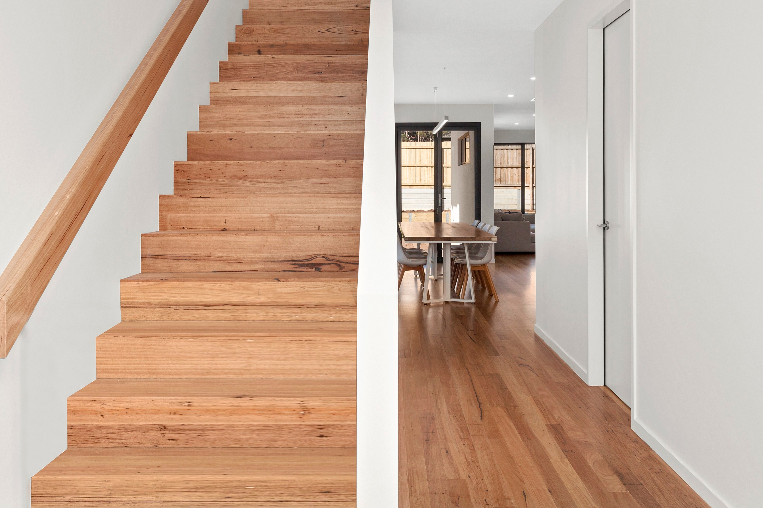 Hardwood floor in a home with flight of stairs
