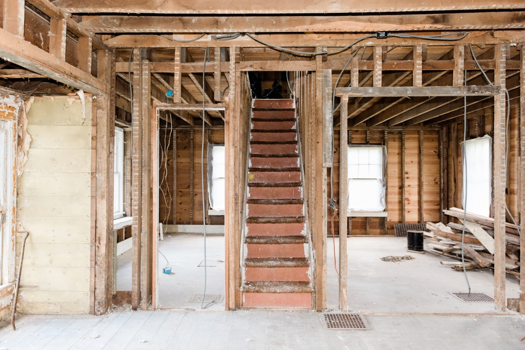 Brown stair case of home undergoing gut rehab