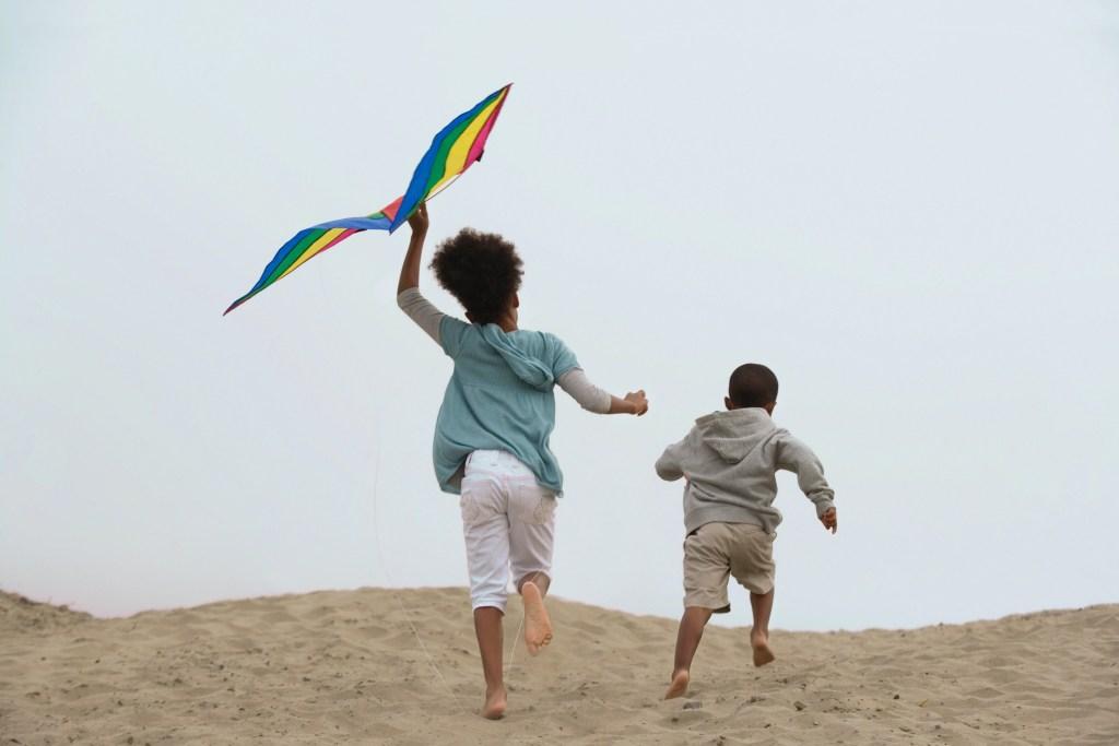 Kids flying kites at the beach