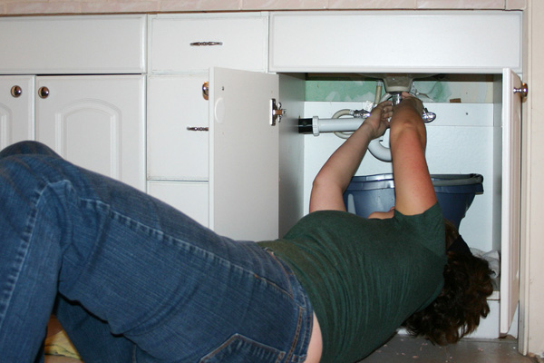 Woman fixing a leaking sink