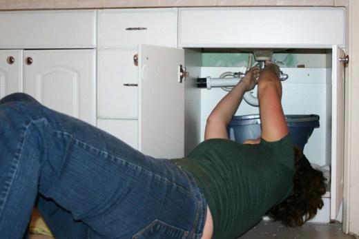 Woman fixing a leaking sink