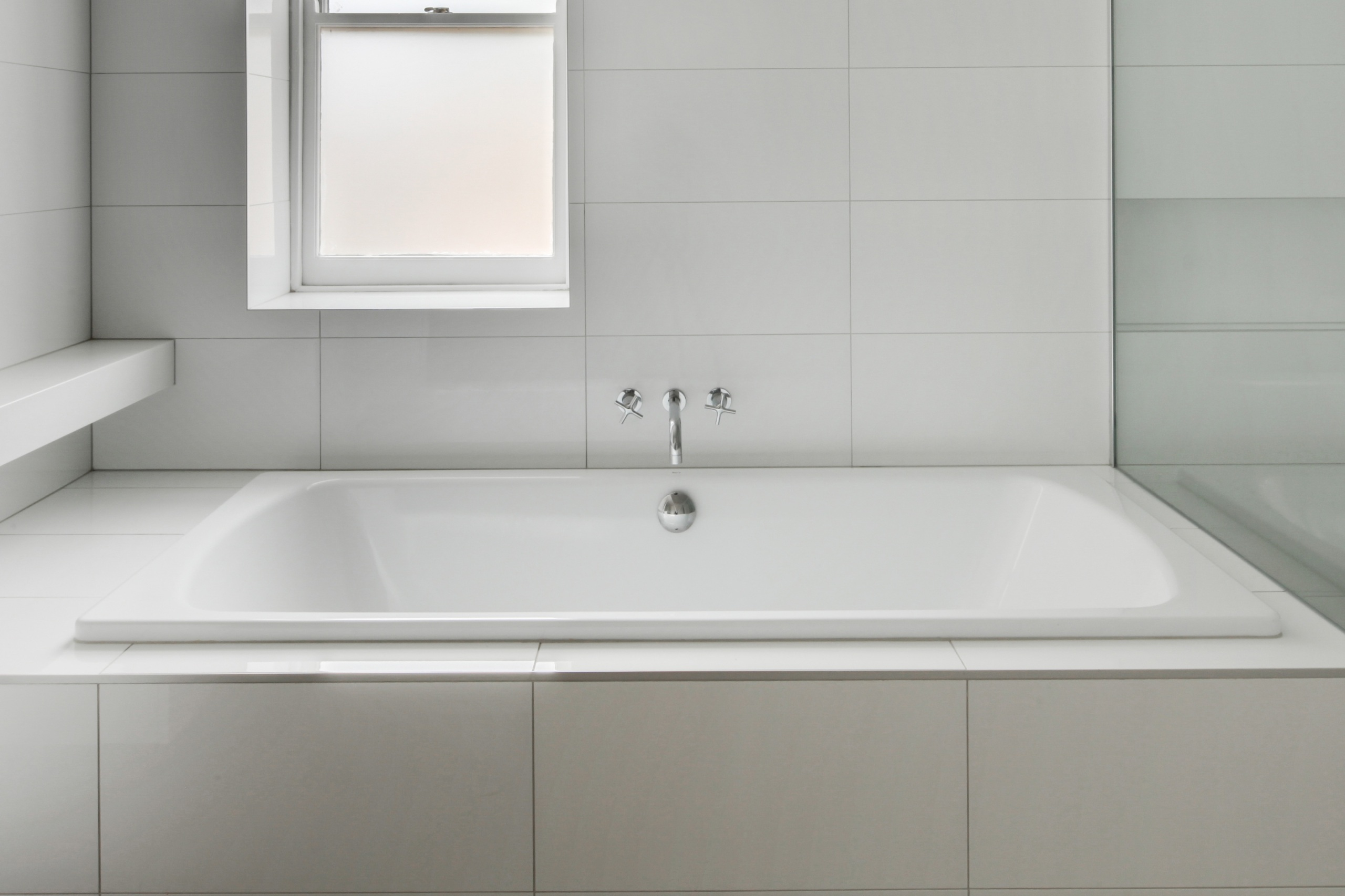 A stark, white tile bathroom with a tub and window