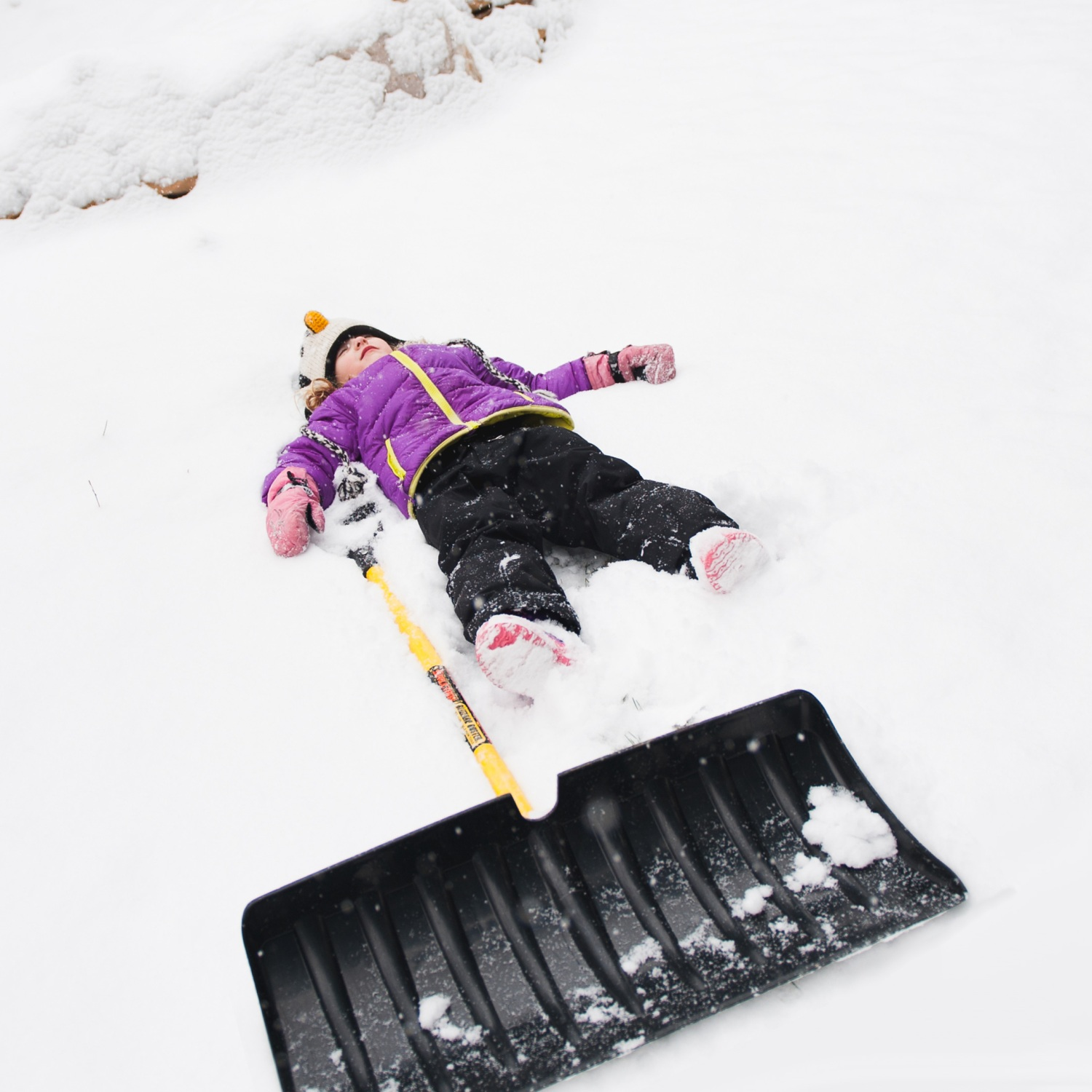 Kid lying next to shovel in snow