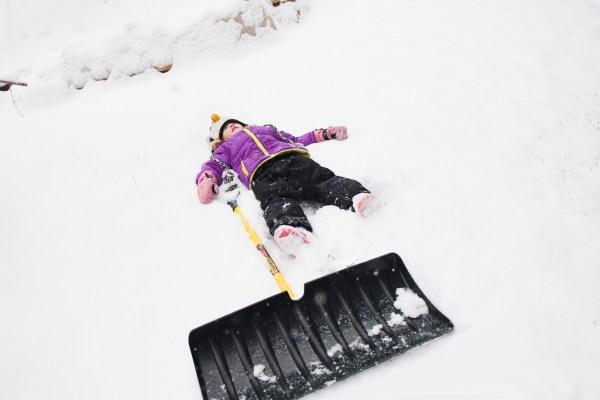 Kid lying next to shovel in snow