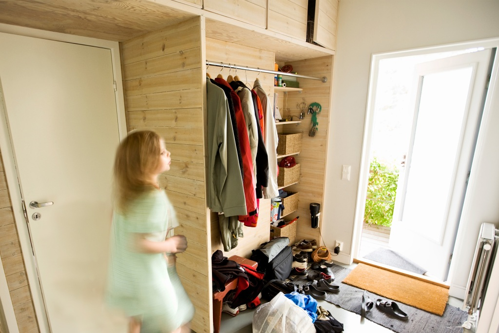 Girl running out of her front door past entryway storage