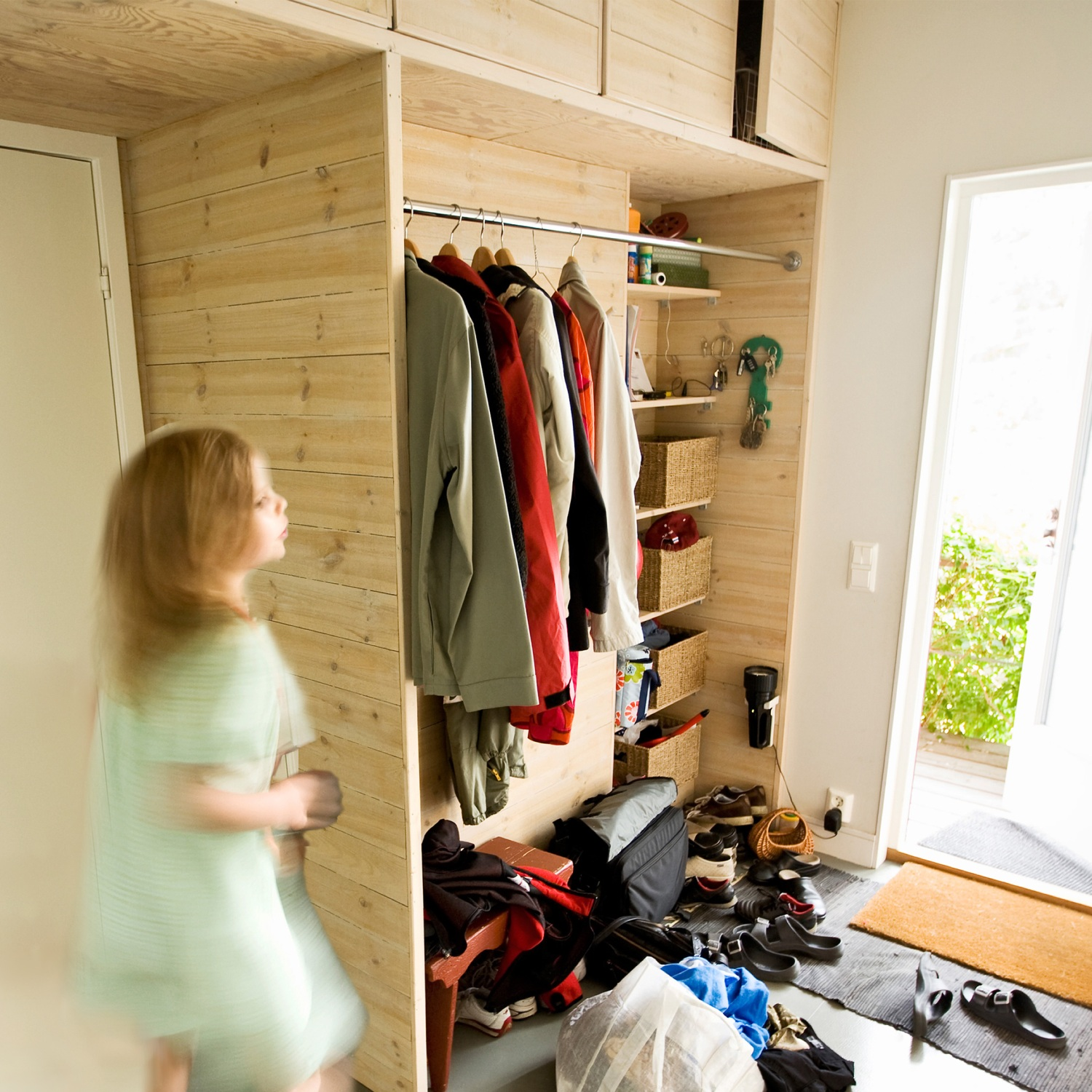 Girl running out of her front door past entryway storage