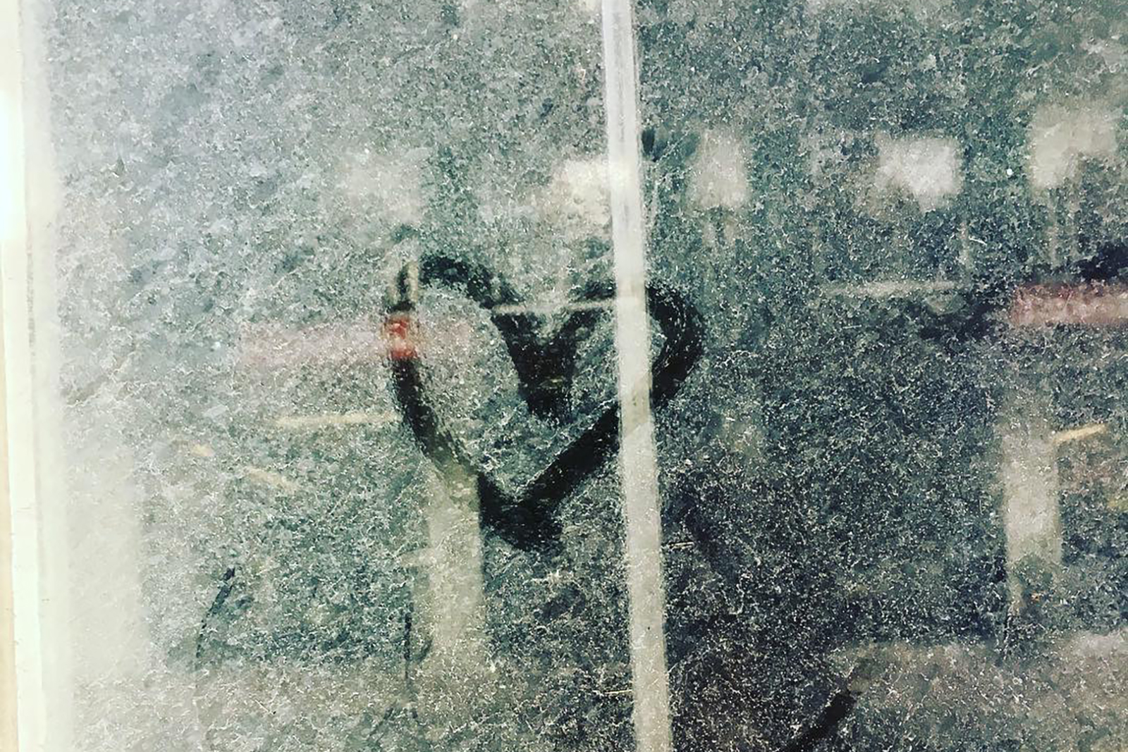 A dirty, dusty window with a heart