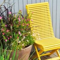 Geltona kėdė su vazoniniu augalu