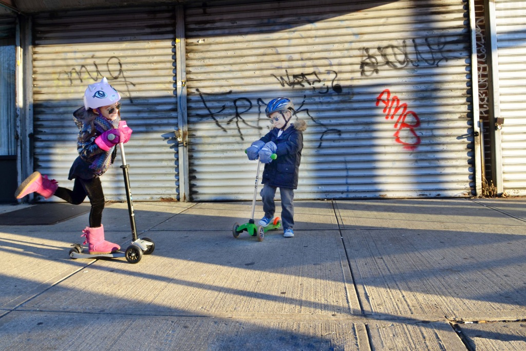 Kids riding their scooters on an urban sidewalk
