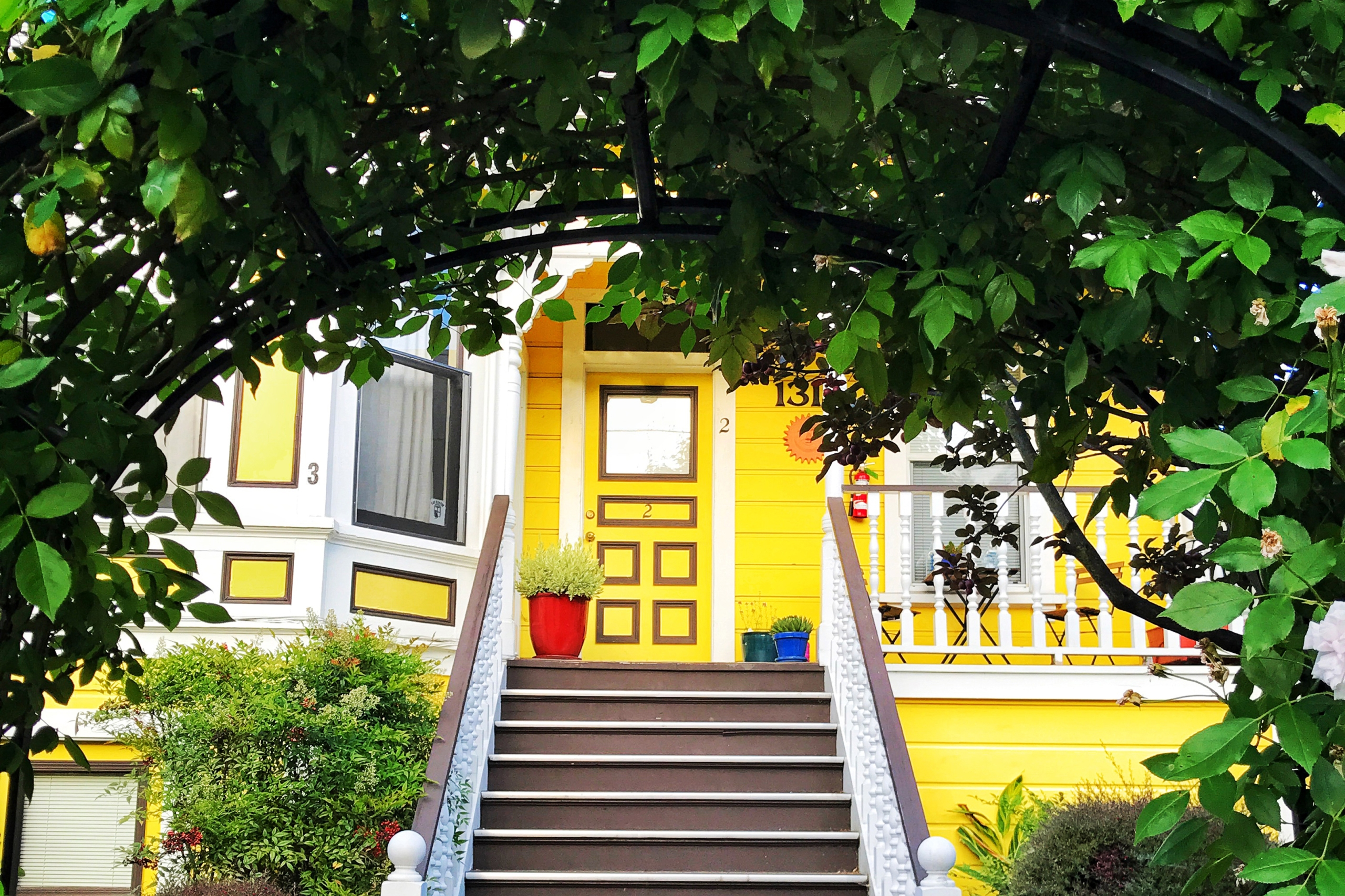Foliage archway framing front steps and yellow door