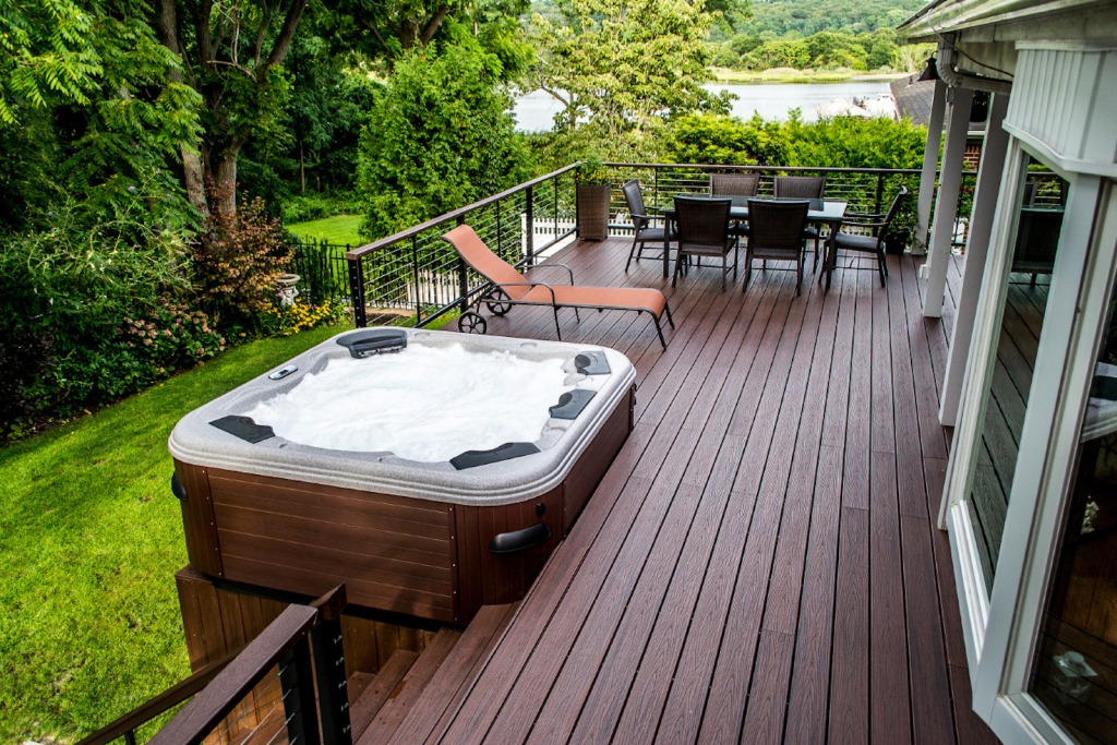 Wood deck with hot tub overlooking lush green area