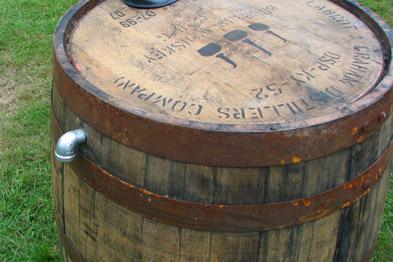 Wooden rain barrel repurposed from wine barrel