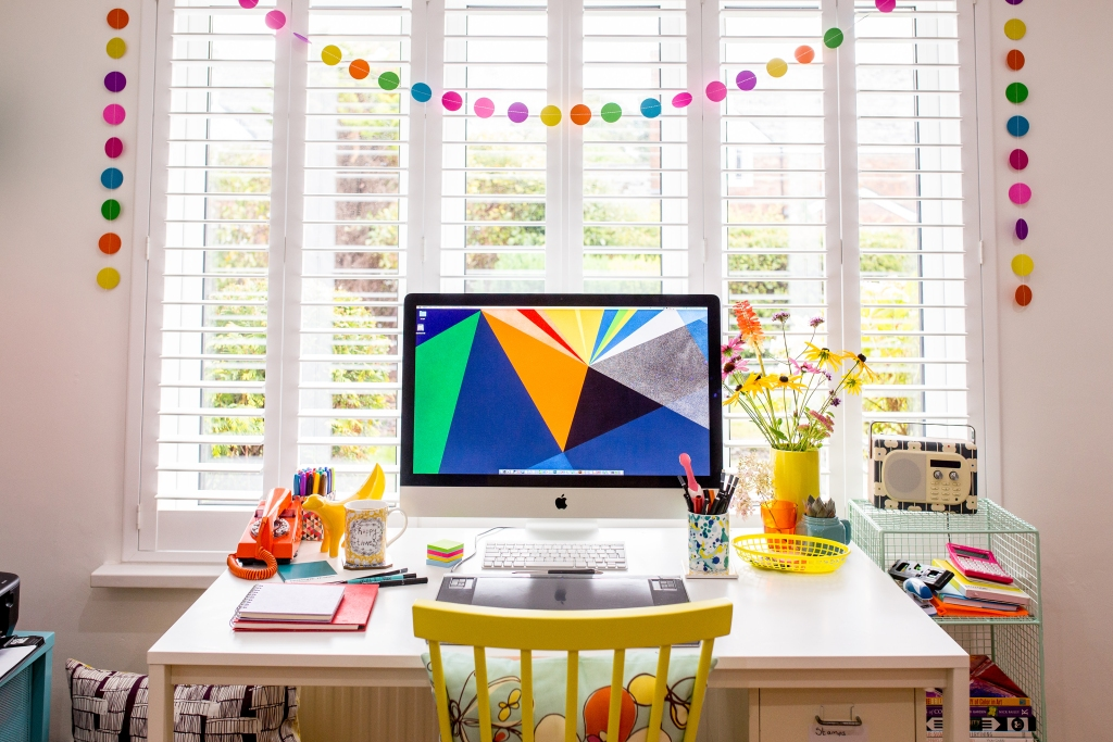 Computer with colorful desktop on desk with bunting behind