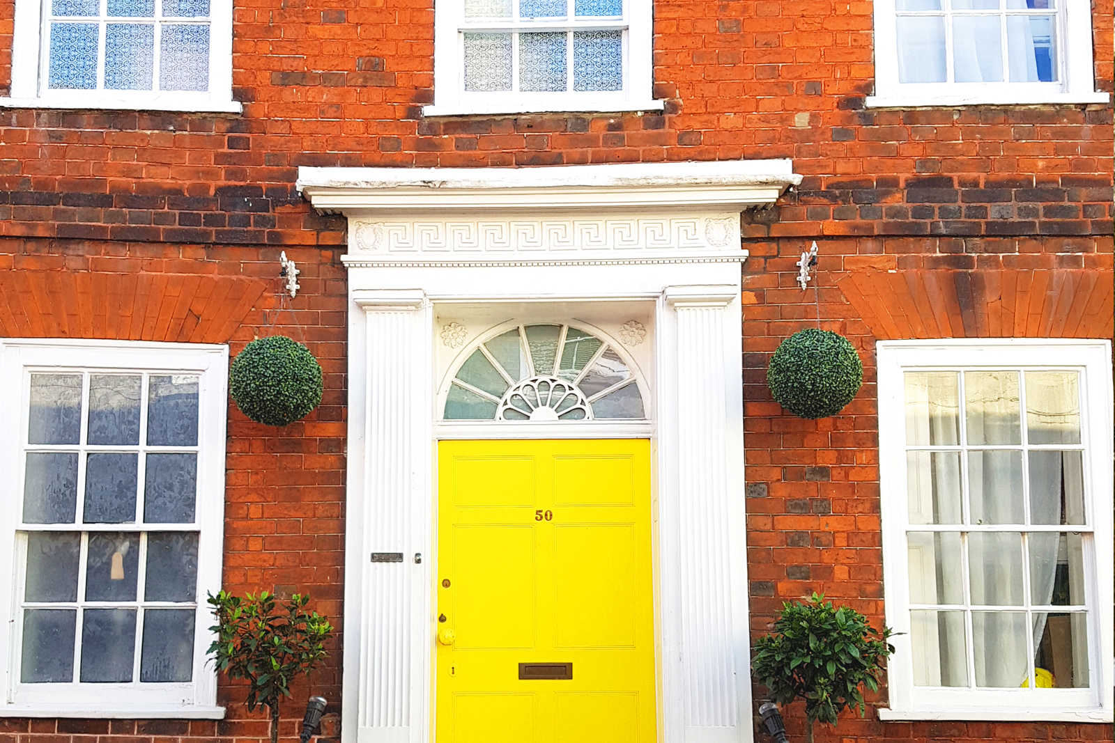 Red brick exterior with yellow front door and white trim