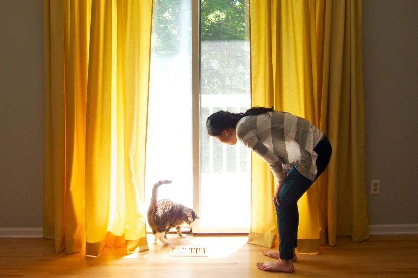 Woman and her cat standing in front of sunny yellow curtains