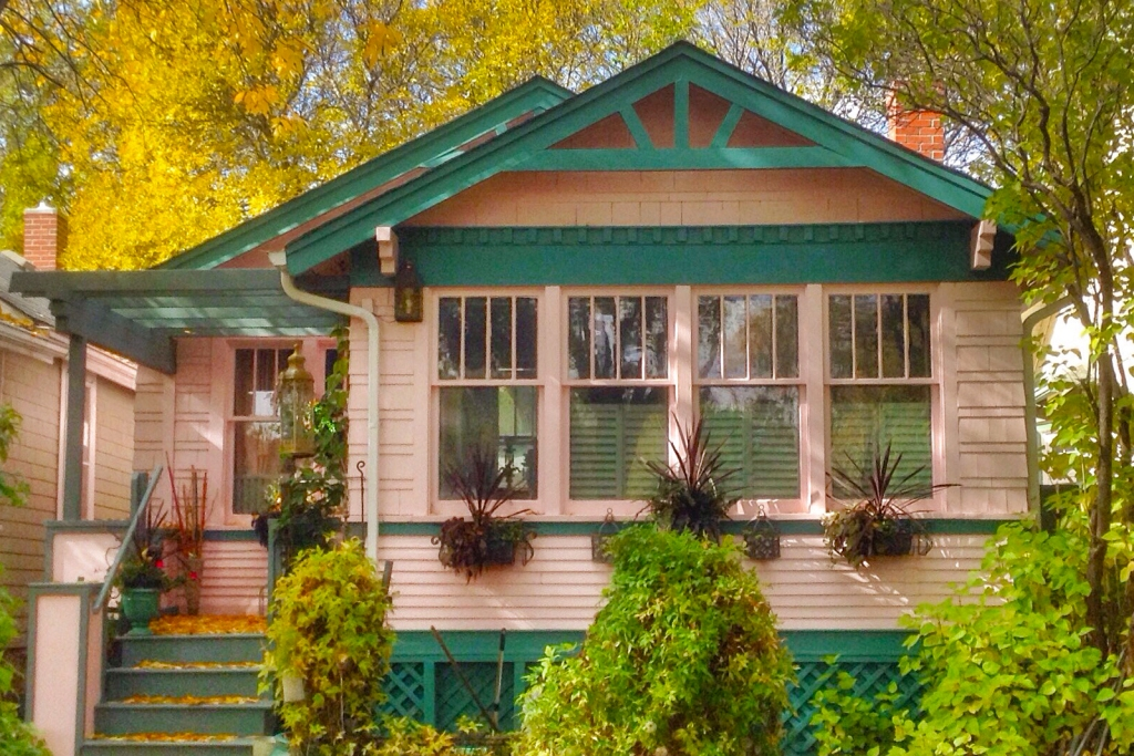 Pink wood-sided house with green trim against autumn foliage