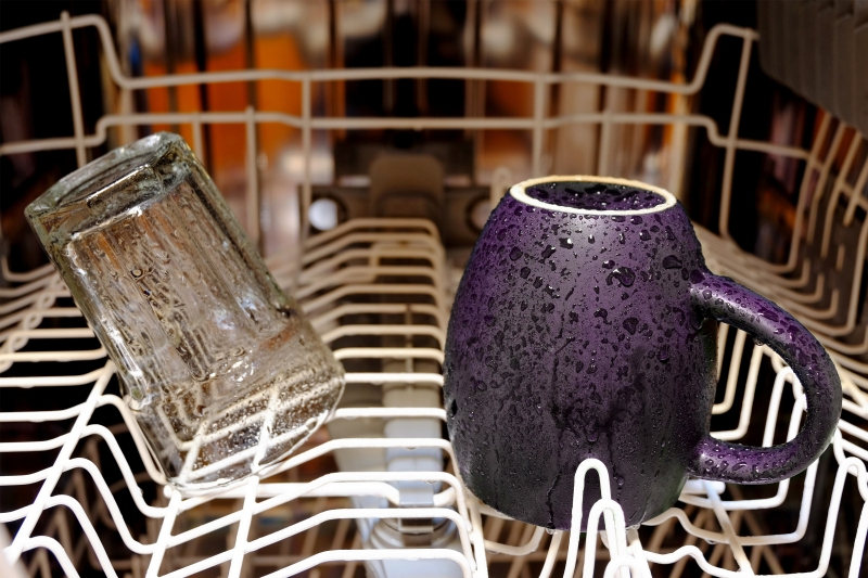 Inside of a wet dishwasher with few items inside