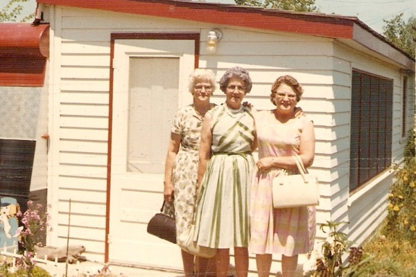 Three old ladies in front of a white building