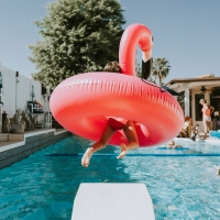 Rear view of girl jumping with a plastic flamingo into pool
