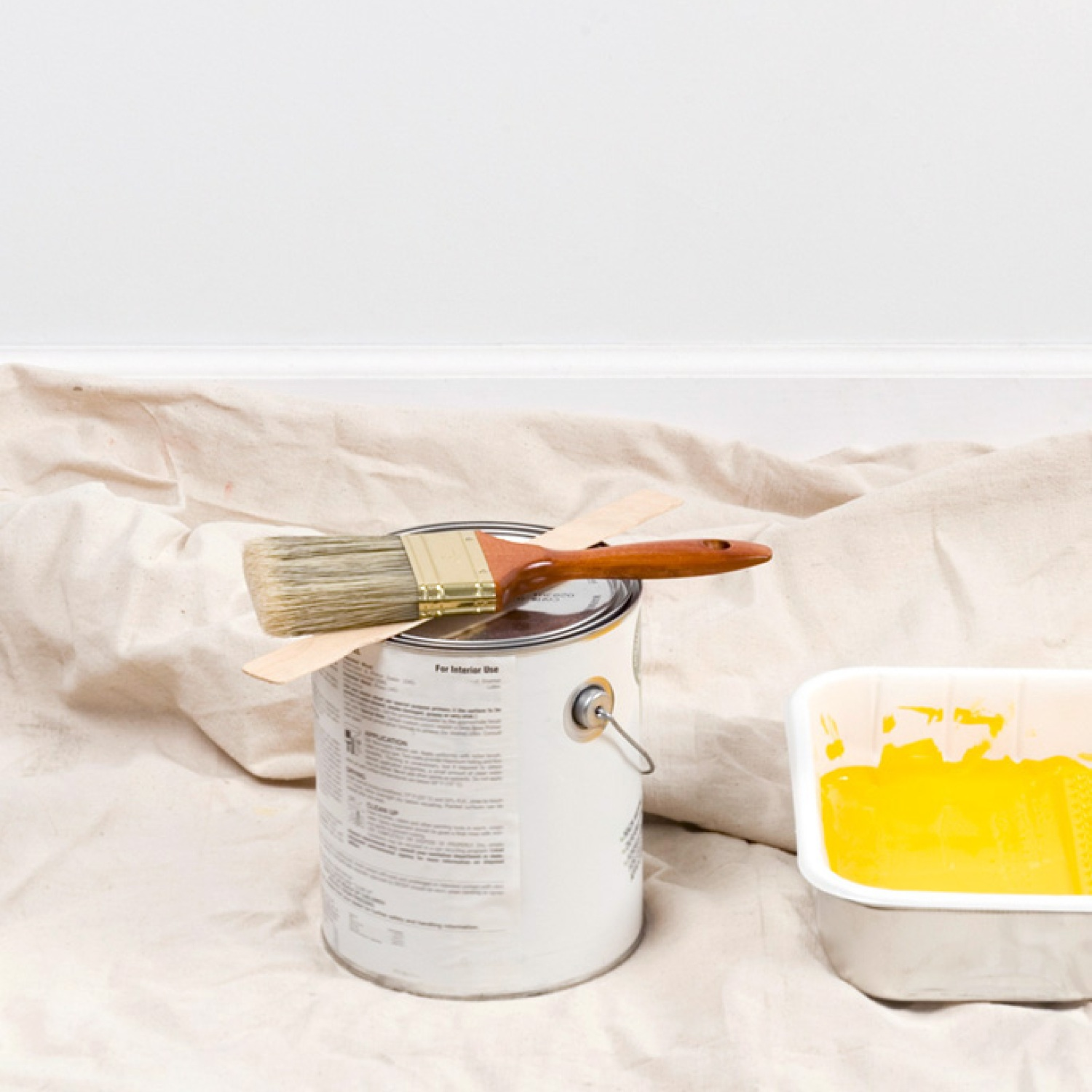 Painting supplies and yellow wall paint