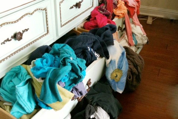 Messy clothing hanging out of drawer