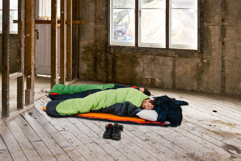 Couple in sleeping bags during home renovation